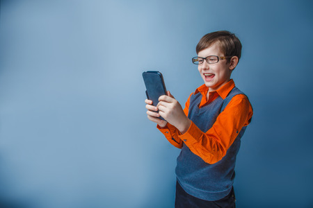plays: European-looking  boy of ten years  in  glasses holding tablet in hand, plays, pleasure on a blue background