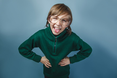 teases: European-looking  boy of  ten years shows  tongue teases on a blue background Stock Photo