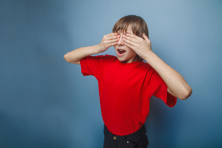 eyes opened: boy in red t-shirt teenager brown hair European appearance closed eyes opened his mouth hands on a gray background, surprise