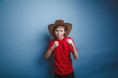 bandana western: boy teenager European appearance in a red shirt brown hat clenched his fists on a gray background, the fight