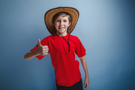 bandana western: boy teenager European appearance in a red shirt brown hat showing sign yes on a gray background, smile