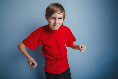 youth crime: boy teenager European appearance in a red shirt holding a brown knife in hand on gray background, anger, attack
