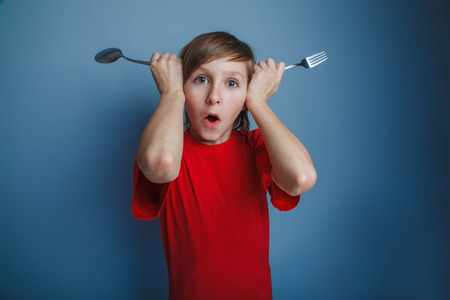 boy teenager European appearance in a red shirt put fork and spoon to the head on a gray background, foolery