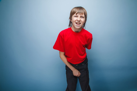 mouth opened: teenager boy in red T-shirt European appearance brown hair holds his hand over the lower abdomen wrinkled mouth opened on a gray background