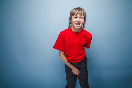 mouth opened: teenager boy in red T-shirt European appearance brown hair holds his hand over the lower abdomen wrinkled mouth opened on a gray background, prostatitis