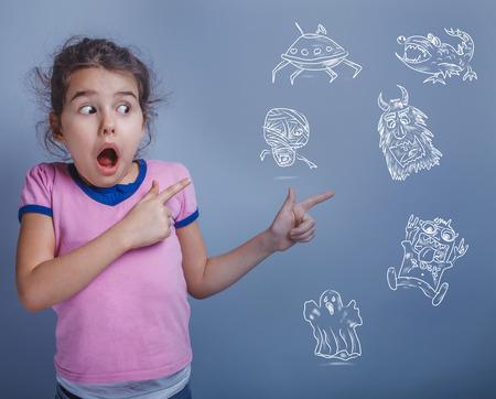 psicologia infantil: muchacha adolescente seis años fobia miedo de monstruos infografías miedo infantil sobre un fondo azul Foto de archivo
