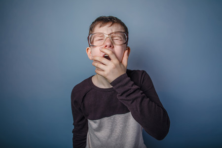 drowsiness: teenager boy of European appearance with glasses covers her mouth yawns on a gray background, drowsiness, fatigue