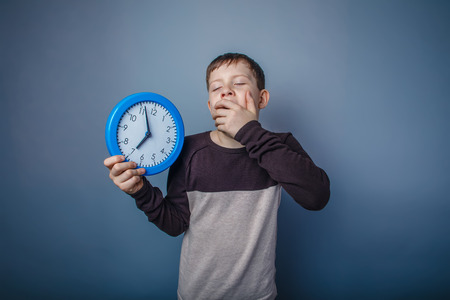 drowsiness: boy teenager European appearance in brown sweater holding a clock shut her mouth yawning on gray background time, drowsiness