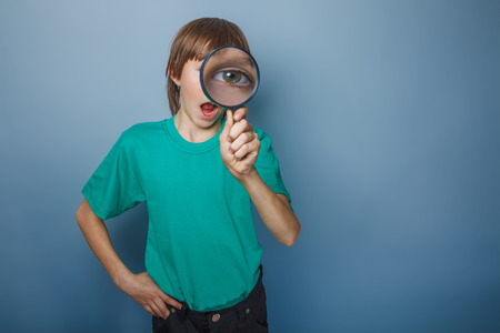 teenager boy brown European appearance in a green shirt looking through a magnifying glass eye opened his mouth on a gray background, knowledge, wonder photo