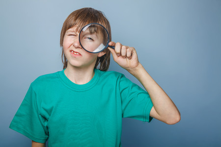 teenager boy brown European appearance in a green shirt looking through a magnifying glass eye wrinkled on gray background, knowledge, curiosity photo