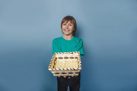 ten empty: European-looking  boy of  ten  years  holding an empty basket in hand on gray background