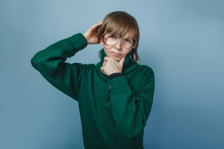 European-looking boy of ten years  in glasses thinking on a gray background photo