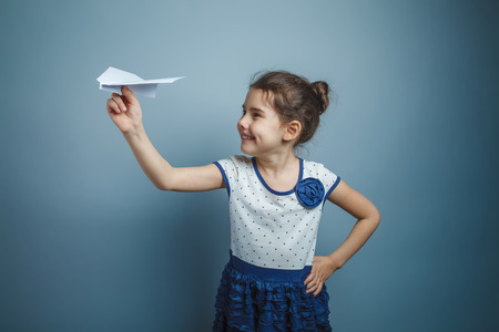 a girl of seven European appearance brunette holding a paper air Banque d'images