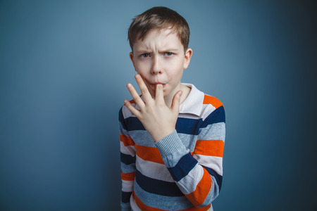 licking finger: teenager boy of about ten European appearance Brown put his inde Stock Photo