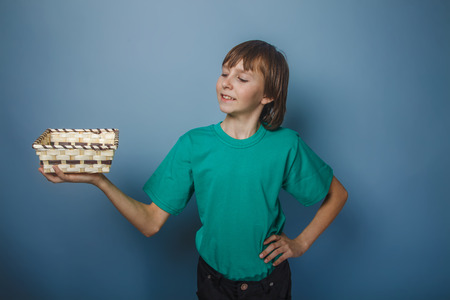 bask: European appearance teenager boy in green t-shirt holding a bask Stock Photo