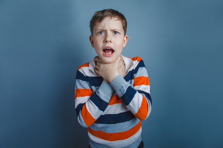 European-looking boy of ten years strangles himself hands on a gray background Stock Photo