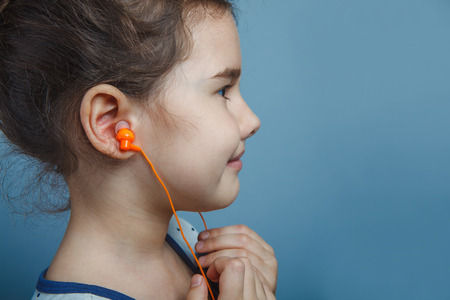five years': Girl European appearance five years listening to music Stock Photo