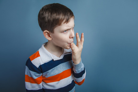 licking finger: European-looking boy  of ten  years licks his finger