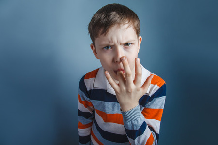 finger licking: European-looking boy  of ten years licks his finger