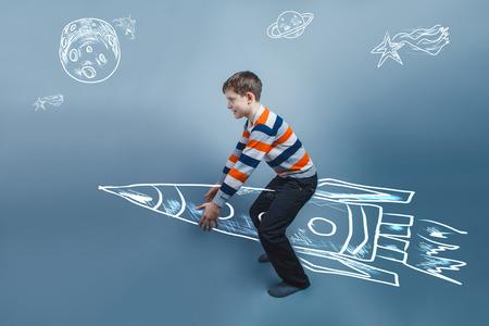 raises: European-looking boy of ten years raises an invisible object on Stock Photo
