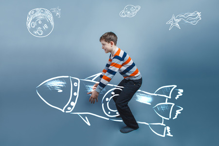 invisible object: European-looking boy of ten years raises an invisible object on Stock Photo