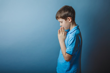 christian youth: boy teenager European appearance in a blue shirt brown praying c