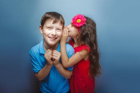 teen boys: Teenage girl whispering in the ear of teen boys on a gray backgr