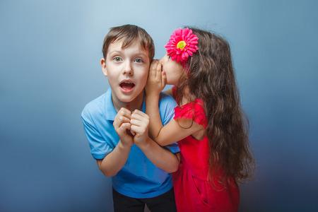 teen boys: Teenage girl whispering in the ear of a secret teen boys on a  g