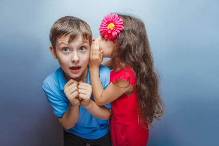 teen boys: Teenage girl whispering in the ear of teen boys  on a gray  back