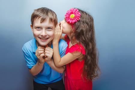Teenage girl whispering in the ear of teen boys on a gray  backg
