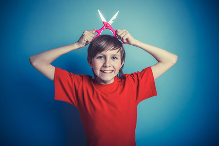 hand in mouth: European-looking boy of twelve  scissors in  hand, mouth open on Stock Photo