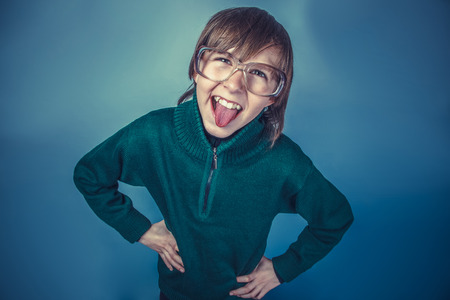 teases: European-looking  boy of  ten years shows tongue teases on a blu Stock Photo