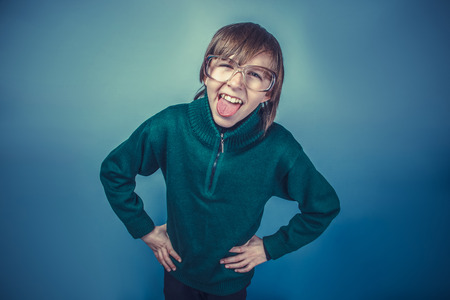 teases: European-looking  boy of ten years shows tongue teases on a blue Stock Photo