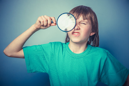 European-looking boy of ten  years holding a magnifying glass, a photo
