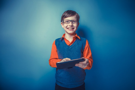 European-looking boy of ten  years in glasses holding tablet in Stock Photo