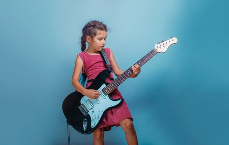 little: Girl European appearance ten years playing guitar on a blue background