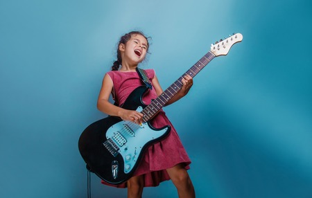 Girl European appearance ten years playing guitar on a blue  background