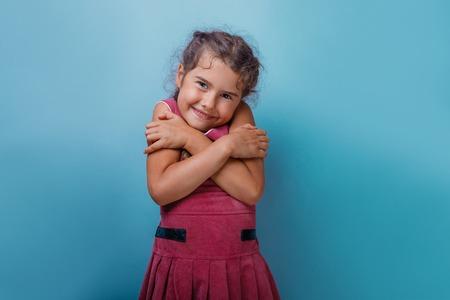 personas abrazadas: Chica década aparición europea abrazándose a sí misma en un fondo azul Foto de archivo