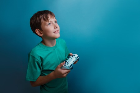 Teen boy of twelve European appearance holds a gaming zhdoystik dreams in the hands of a gray background Stock Photo