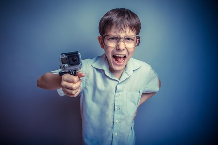yells: A boy of about ten European appearance in light brown shirt and glasses holding a camera and yells EKS on a gray background, videography retro photo effect