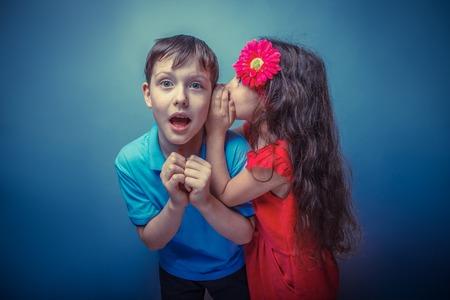 teen boys: Teenage girl whispering in the ear of a secret teen boys on a  gray background retro photo effect Archivio Fotografico