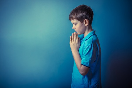 children hands: Boy teenager European appearance ten years stands sideways praying on a gray background retro photo effect