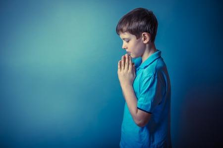 orando: Muchacho adolescente aparición europea diez años está de lado rezando sobre un fondo gris efecto de la foto retro