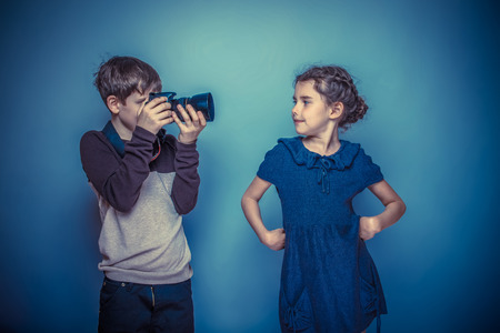 seven years: Teenage boy about seven years old girl photographed on a professional camera on gray background, smiling, model, pose retro photo effect