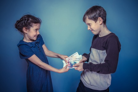 bleed: teenage boy and girl holding money bills in his hands bleed each other on gray background retro photo effect Stock Photo