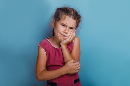decade: Girl European  appearance decade toothache on  blue background Stock Photo