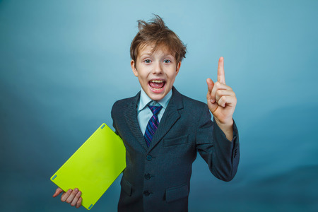 wild hair: Teen boy businessman in a suit raised his finger up wild hair holding a tablet