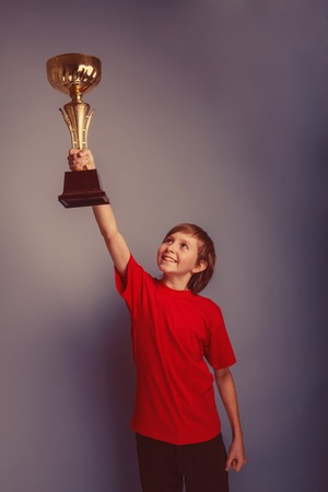 lifted hands: boy teenager European appearance in a red shirt lifted the cup in his hands on a gray background, the reward retro