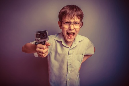 yells: A boy of about ten European appearance in light brown shirt and glasses holding a camera and yells EKS on a gray background, videography retro Stock Photo