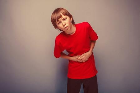 abdominal pain: Adolescente del muchacho de doce a�os en la camisa roja dolor abdominal, gastritis, diarrea retro